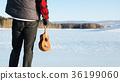 Man with ukulele on a frozen lake 36199060
