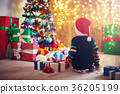 Boy and sitting on the floor with presents near 36205199