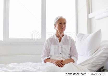 sad senior woman sitting on bed at hospital ward 36212767