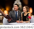 couple taking menu at christmas restaurant 36213642