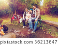 happy family sitting on bench at camp fire 36213647