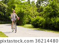 happy woman riding fixie bicycle in summer park 36214480