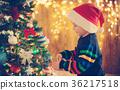 Boy standing near christmas tree 36217518