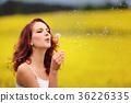 beautiful woman blowing dandelion in the field 36226335