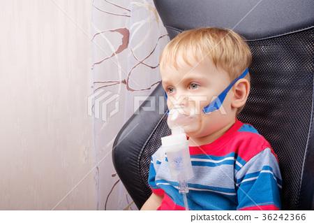 Boy making inhalation with a nebulizer 36242366