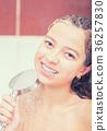 Teenage girl in bathroom is showering.  36257830