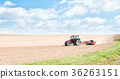 Tractor compresses the soil with rollers. 36263151