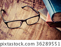 Glasses placed on a wooden table with books. 36289551