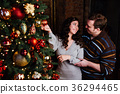 Young couple in love decorates a Christmas tree at 36294465