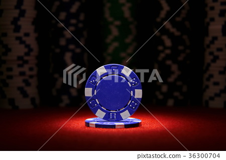 Closeup of blue poker chip on red felt card table  36300704