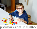 Little blond child with eye glasses playing with 36308827