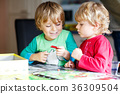 Two little blond kid boys playing together board 36309504