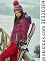 Sporty female holds snowboard in mountains 36320304
