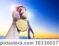 Businessman hand holding golden coin medal. 36330037