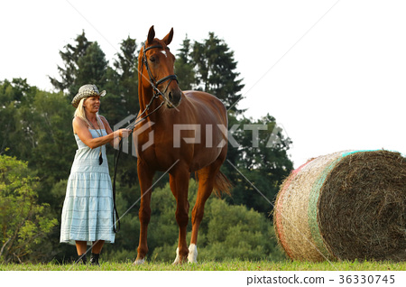 Farmer woman stay beside horse near hay bale 36330745