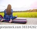 Woman traveler admiring yellow rice field scenery 36334262