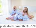 Kids in bed. Children in pajamas. Family bedroom. 36340270