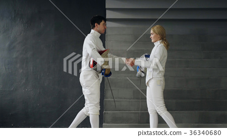 Two fencers man and woman shake hands each other 36340680