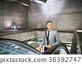 Businessman on an escalator on a metro station. 36392747
