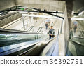 Businessman on an escalator on a metro station. 36392751