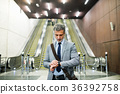 Businessman in front of escalators on a metro 36392758