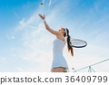 Woman playing tennis giving service 36409799