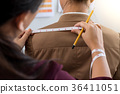 Young woman dressmaker or designer working as measuring for clot 36411051