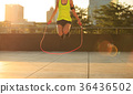 woman jumping rope at sunrise city building roof 36436502