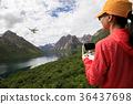 asian woman photographer flying drone outdoors 36437698