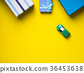 Gift boxes and toy car on yellow background 36453638