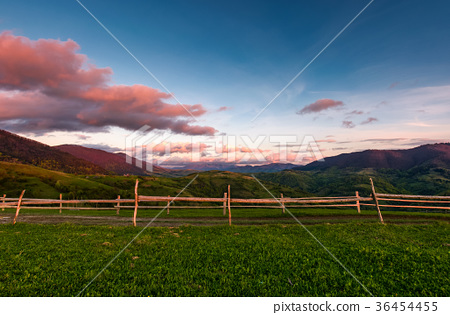 wooden fence on a grassy hill at sunset 36454455