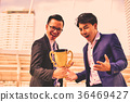 Young businessmen are competing for wins and trophies. 36469427