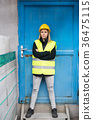 Woman worker standing outside a warehouse. 36475115