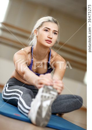 Attractive slim blonde female doing stretching 36475275
