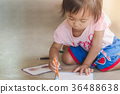 Little girl drawing with color pencil on paper 36488638