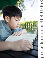 Asian Cute little boy reading book with serious face . 36491063