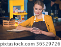 Outgoing worker writing message in phone 36529726