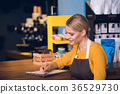 Cheerful barista making notes in confectionary 36529730