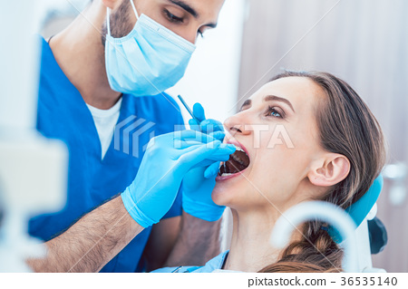 Young woman during painless teeth cleaning done by 36535140