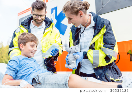 Emergency medic giving soft toy to console injured 36535185
