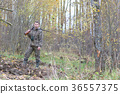 Man in camouflage and with guns in a forest belt 36557375