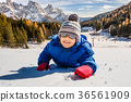 smiling baby lying on the snow 36561909