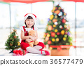 girl sitting on the floor with Christmas tree  36577479