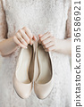 beige shoes in female hands of young bride 36586921