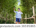 Young guy take a relax in park, sit on green grass and walking in around. 030 36595865