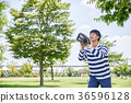 Young guy take a relax in park, sit on green grass and walking in around. 114 36596128