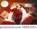 Santa Claus wrapping up Christmas gifts  36603091