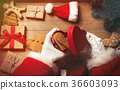 Santa Claus wrapping up Christmas gifts  36603093