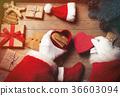Santa Claus wrapping up Christmas gifts  36603094
