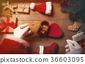 Santa Claus wrapping up Christmas gifts 36603095